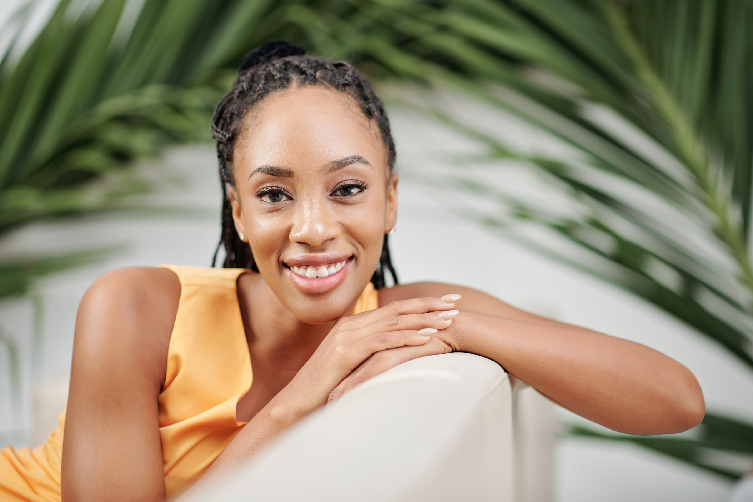 Pretty young Black woman sitting on armchair with palm leaves behid and smiling at camera