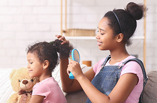 african-teen-girl-combing-younger-sisters-hair-V9RLQUR